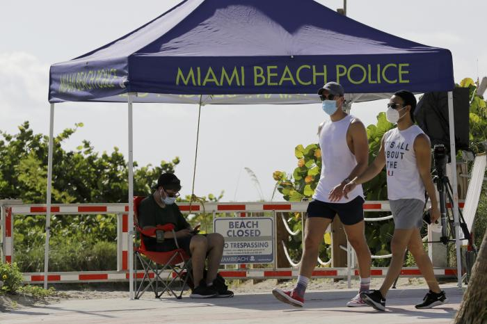 People wearing protective face masks walk past a closed entrance to the beach during the new coronavirus pandemic, Friday, July 3, 2020, in the South Beach neighborhood of Miami Beach, Fla