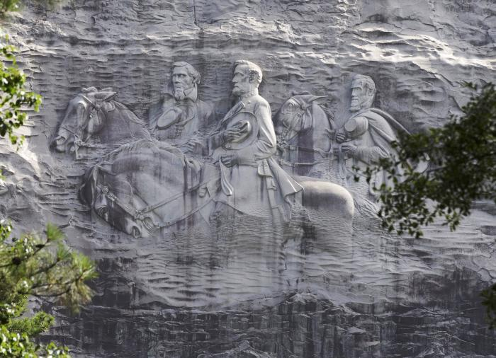 This June 23, 2015 file photo shows a carving depicting Confederate Civil War figures Stonewall Jackson, Robert E. Lee and Jefferson Davis, in Stone Mountain, Ga. The sculpture is America's largest Confederate memorial. (AP Photo/John Bazemore, File)