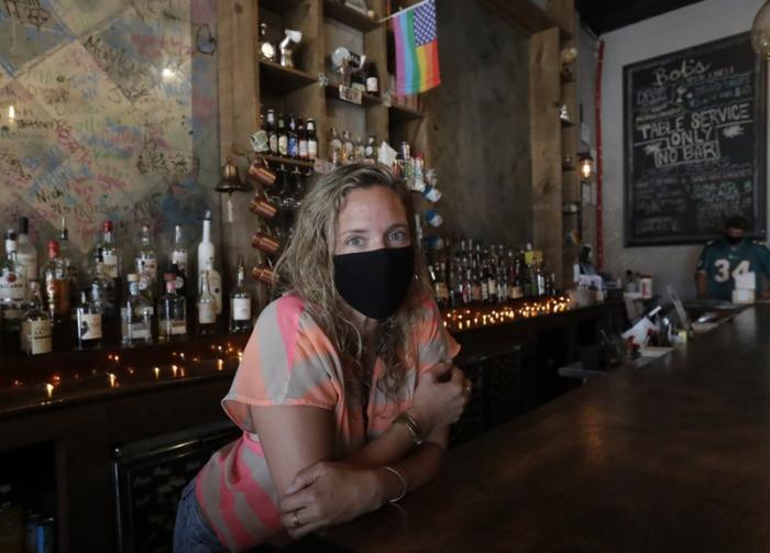 Danielle Savin, co-owner of a bar called Bob's Your Uncle, poses for a photo, Tuesday, June 30, 2020, at the bar in Miami Beach, Fla.
