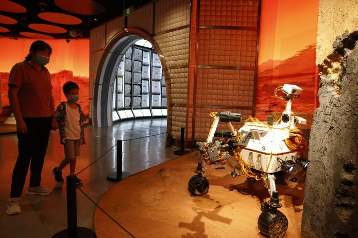 A woman and child wearing masks to curb the spread of the coronavirus look at a model depicting a rover on Mars during an exhibition in Beijing Thursday, July 23, 2020