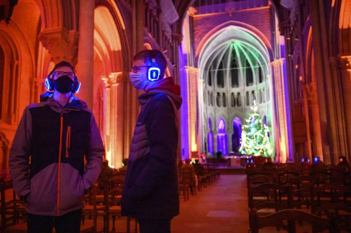 "People wearing protective face masks listen with headphones on Christmas Eve during a ""silent disco"" event called ""The Silent Night, Christmas in the Ears"" at the Lausanne Cathedral in Lausanne, Switzerland"