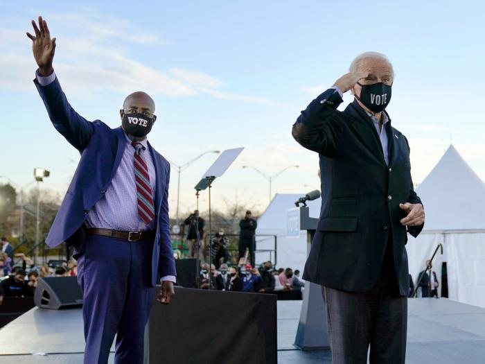 In this Monday, Jan. 4, 2021 file photo, President-elect Joe Biden, right, campaigns for Senate candidates Raphael Warnock, left, and Jon Ossoff, not pictured, in Atlanta