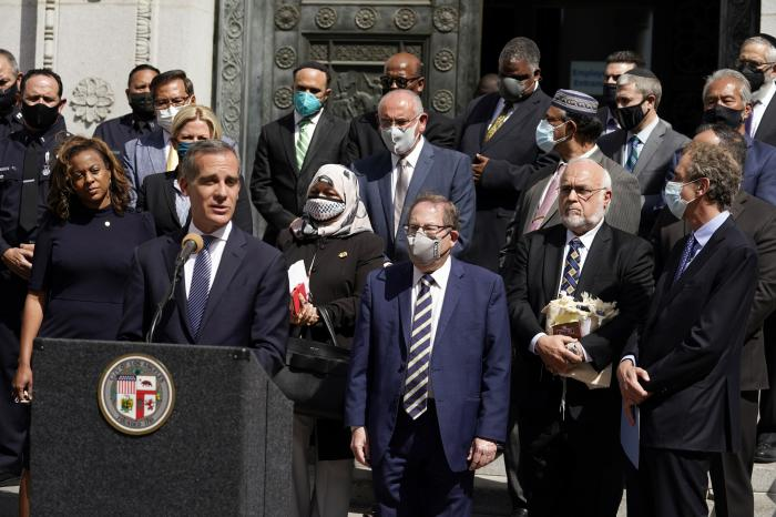 In this Thursday, May 20, 2021, file photo, Los Angeles Mayor Eric Garcetti, at podium, speaks in front of civic and faith leaders outside City Hall in Los Angeles.